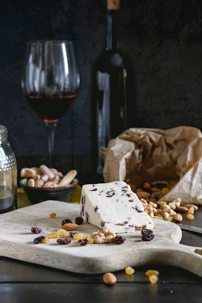 Wensleydale with cranberry cheese on a wooden cutting board, with nuts and red wine in the background