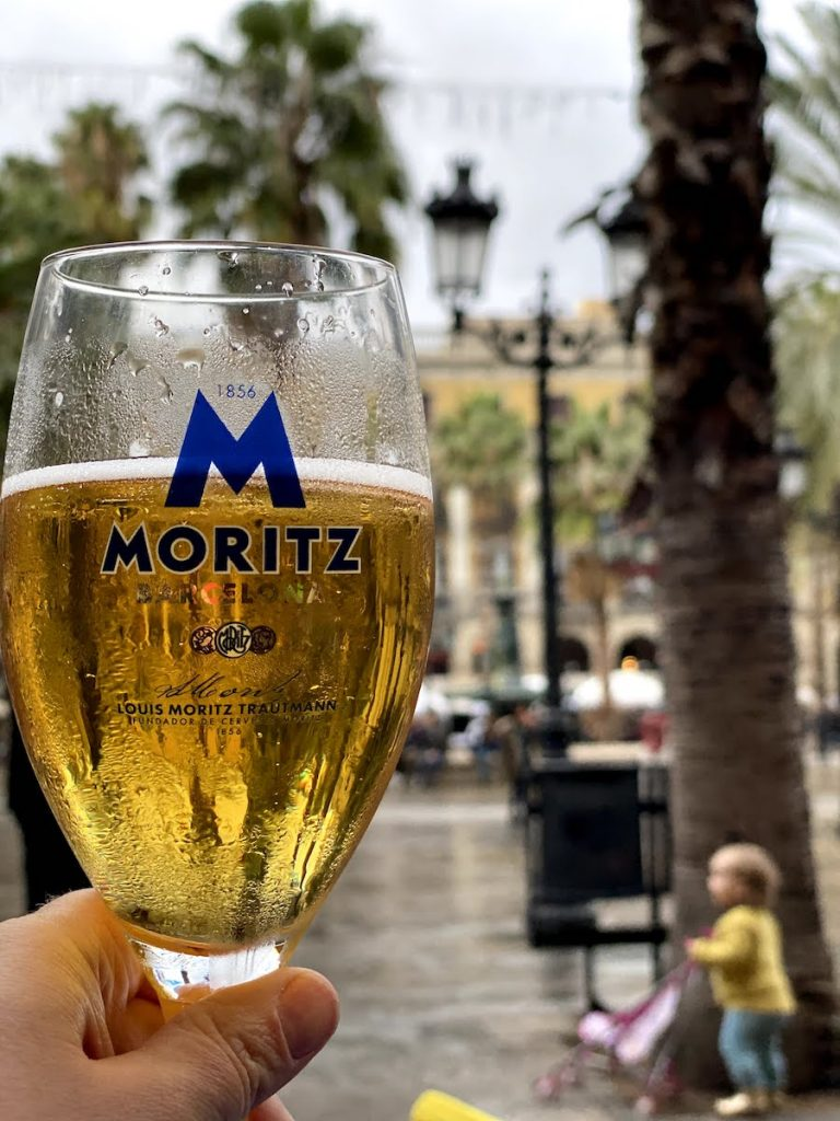 A woman's hand holding a glass of Moritz Lager in the foreground with Plaça Reial in Barcelona in the background
