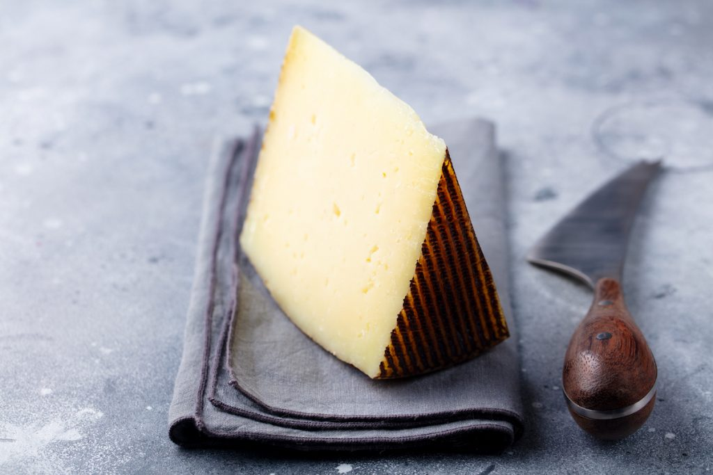 A wedge of manchego cheese sits on a cloth napkin with a cheese knife sitting beside