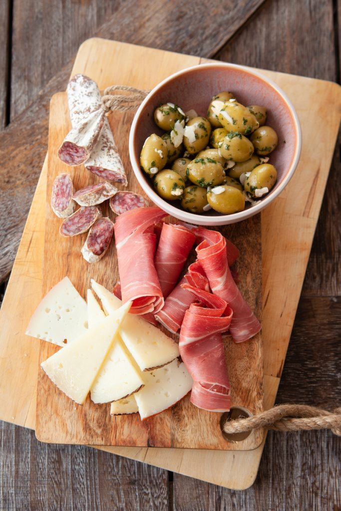 Spanish tapas on a wooden board. Manchego cheese, meat, and green olives