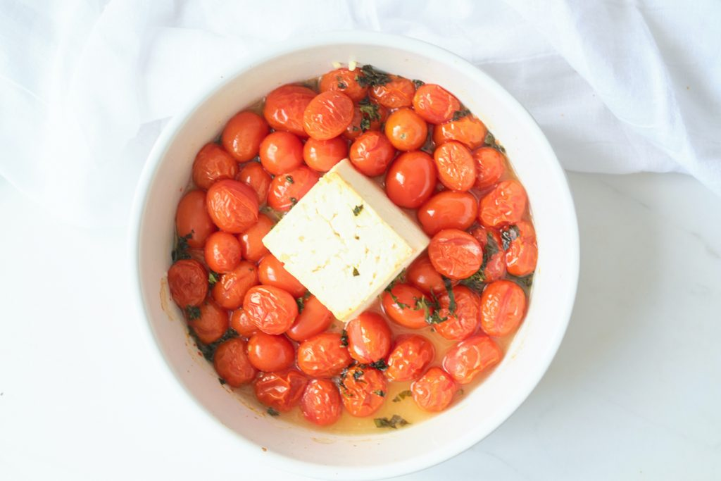 A block of feta cheese in a baking dish surrounded by cherry tomatoes and topped with fresh chopped basil. The photo shows the cooked ingredients, after being baked in a baked feta cheese pasta recipe.
