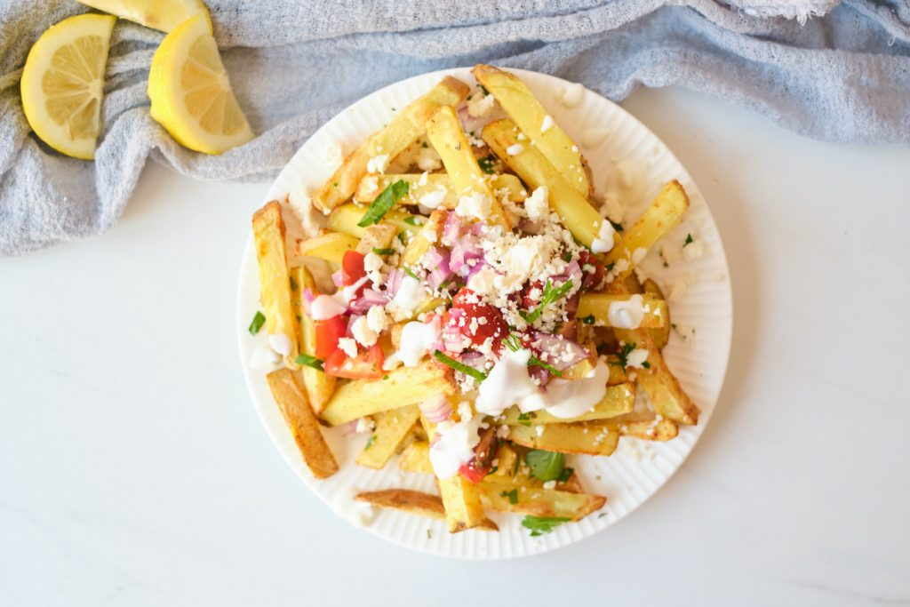 loaded greek fries with feta cheese, tomatoes, parsley, red onion and Tzatziki