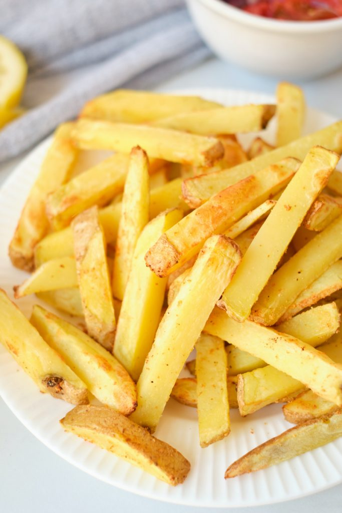 A closeup of freshly made homemade garlic fries on a white plate, with ingredients for Greek fries in smaller dishes mostly out of frame. A dish of tomatoes is partially visible as is part of a lemon wedge.