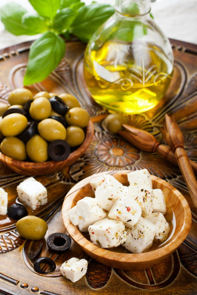 Cubed feta cheese in olive wood bowl and green and black olives on rustic wooden background. Greece is the only country in Europe allowed to produce feta cheese and call it as such.