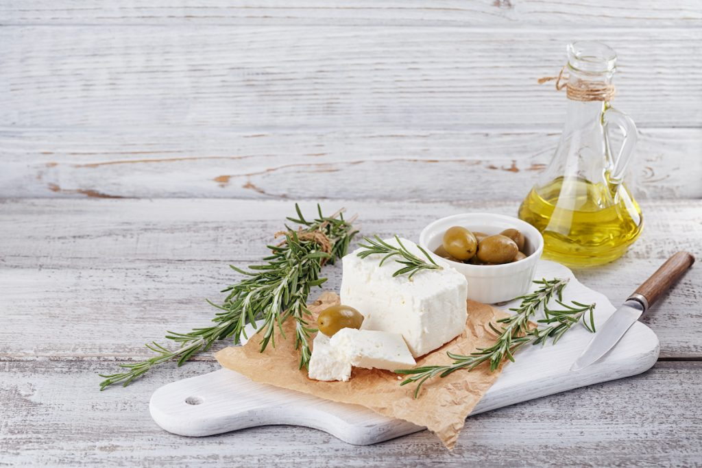Fresh feta cheese with green olives, olives oil and rosemary on white wooden serving board over light wooden background.