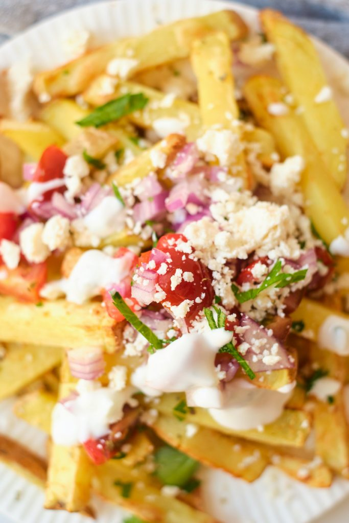 A close up photo of feta fries loaded with Greek toppings, including crumbled feta, red onion, tomatoes, parsley on top of homemade fries