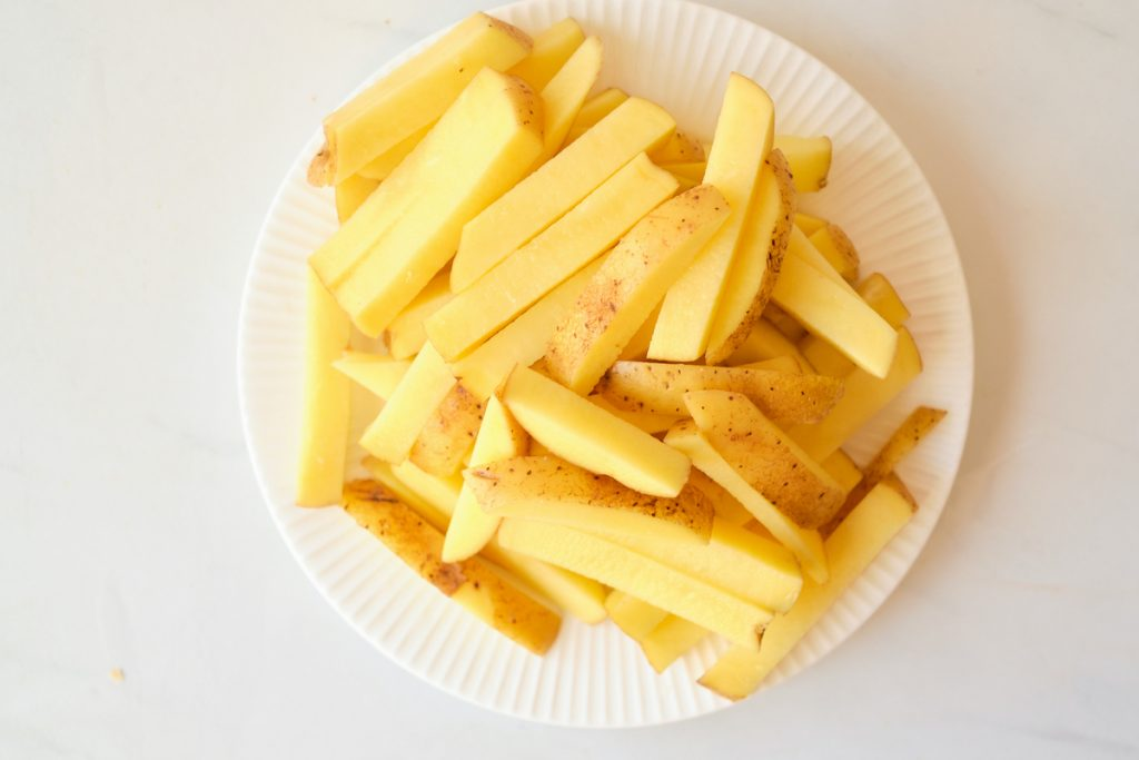Evenly cut strips of russet potatoes with the skin on as being prepared for homemade french fries