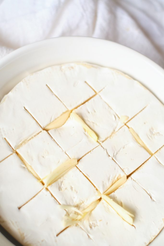 A close up of a wheel of brie in a baking dish. The brie is scored on top and stuffed with garlic slices to illustrate how to bake brie and make a baked brie with garlic and thyme