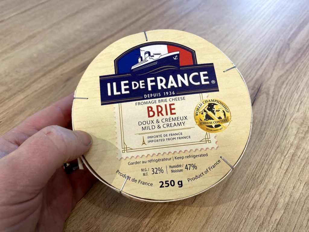 A hand holds a wooden box of Ile de France Brie cheese on a wooden table
