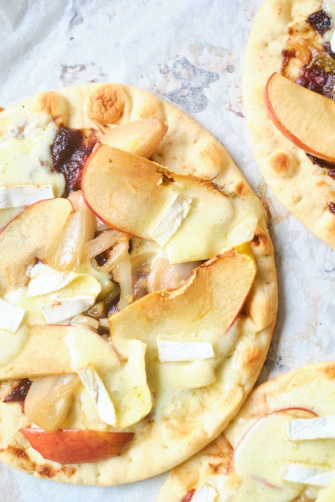 Apple brie pizza after being baked in the oven on parchment paper