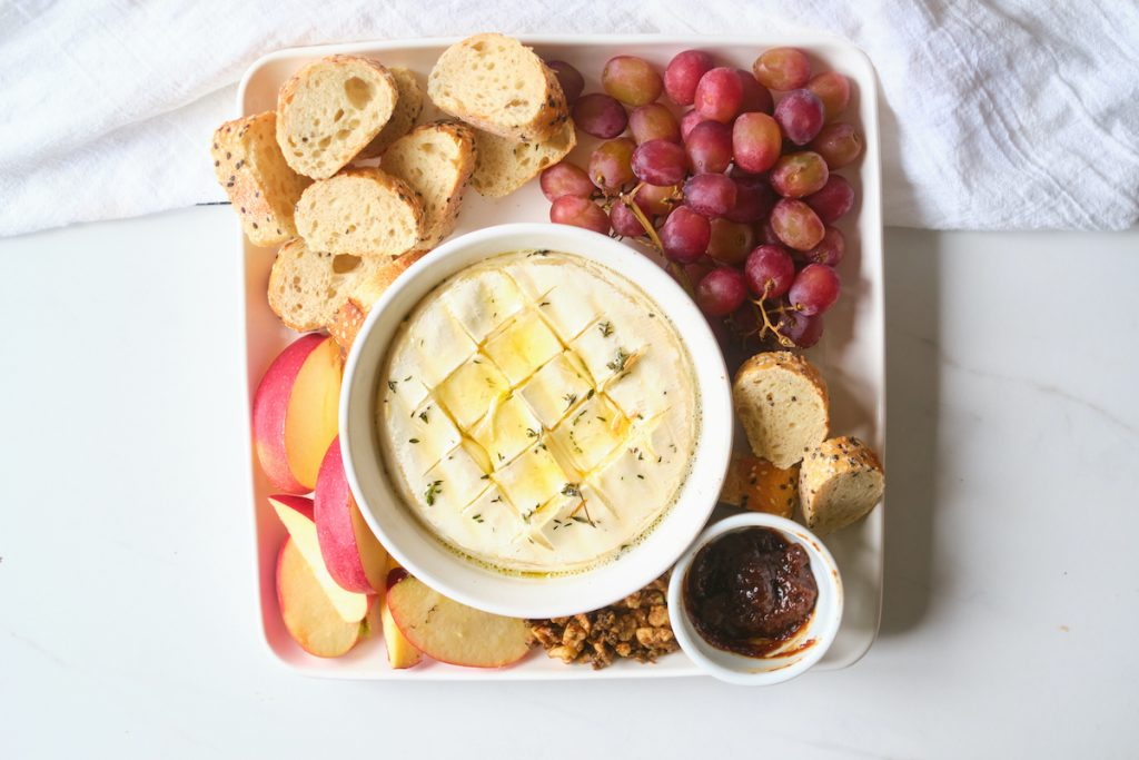 Baked brie with garlic and thyme on a cheese and charcuterie platter