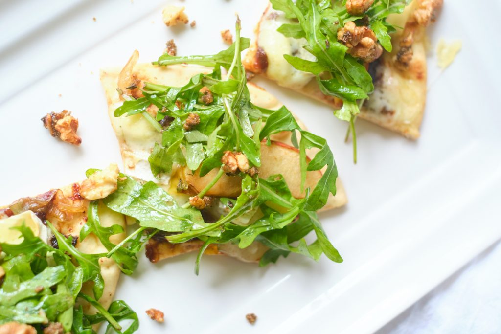 Apple brie pizza topped with candied walnuts and arugula on a white plate
