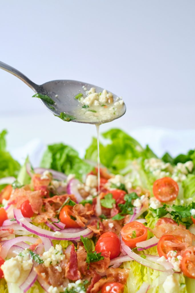 A spoon loaded with gorgonzola vinaigrette drizzling the dressing over a romaine wedge salad