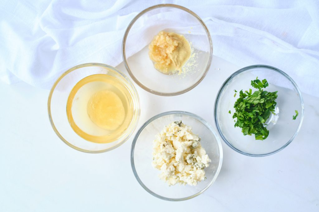 ingredients for a simple gorgonzola vinaigrette in small glass bowls, including white wine vinegar, dijon, gorgonzola, and parsley