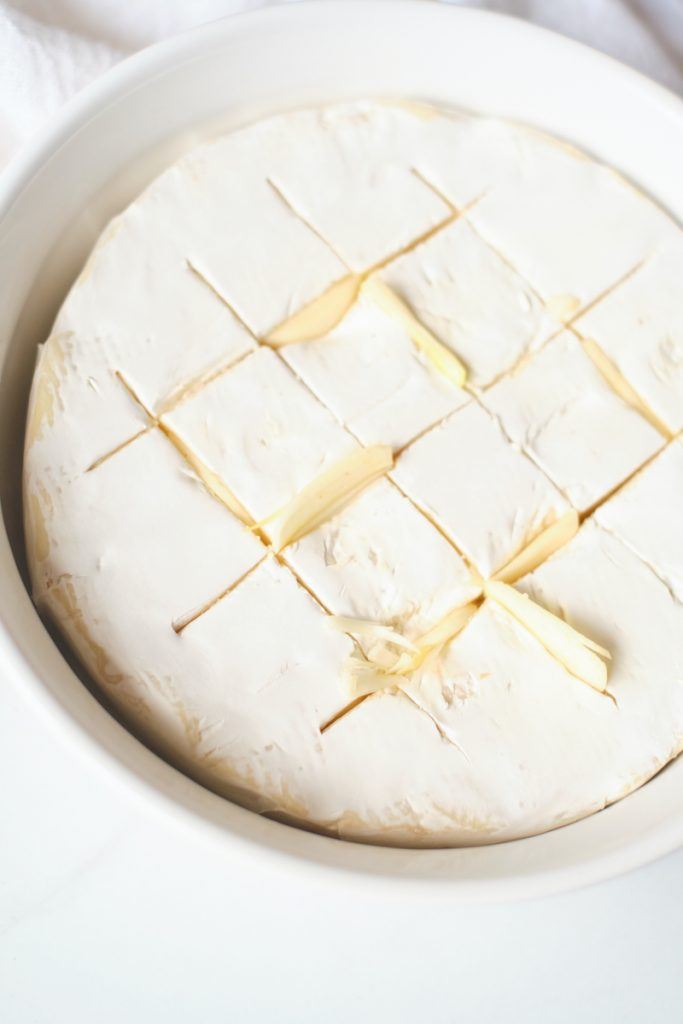 A birds eye view of a wheel of brie in a baking dish. The brie is scored on top and stuffed with garlic slices showing a process of how to bake brie and make a baked brie with garlic and thyme