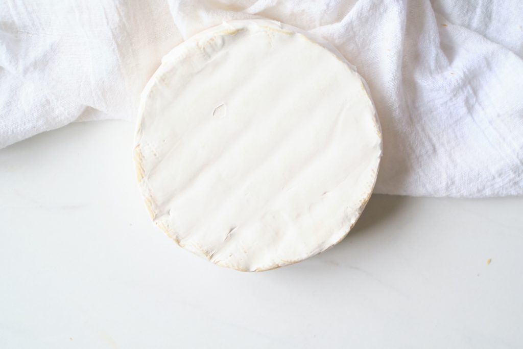 A wheel of brie on a white counter and cloth