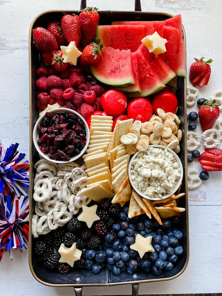 Birds eye view of a fourth of July or Memorial Day cheese and fruit platter arranged in red, white, and blue color blocks