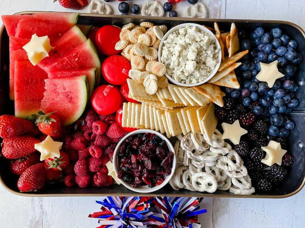 A fruit and cheese board that is color themed for the 4th of July or Memorial day using patriotic red white blue food