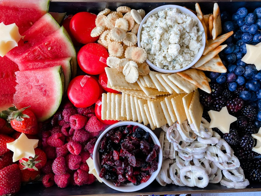 Close up of a fruit and cheese platter blocked into red foods, white foods and blue foods for a patriotic theme