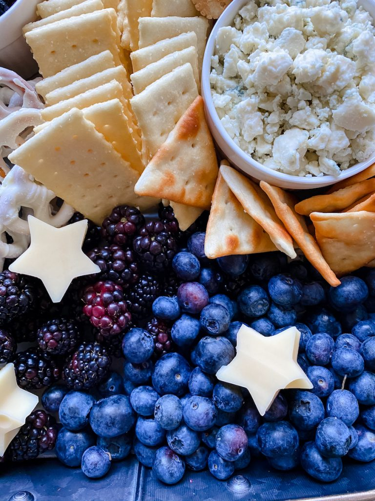 Close up of blueberries, blackberries, cheese stars, blue cheese crumbles and crackers on a fruit and cheese board