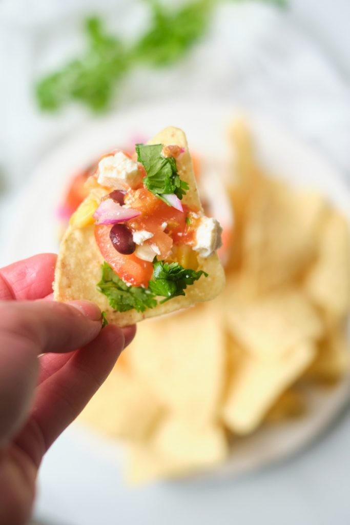 A woman's hand holds a tortilla chip loaded with black bean corn feta dip. A bowl of the dip and plate of tortilla chips are out of focus in the background