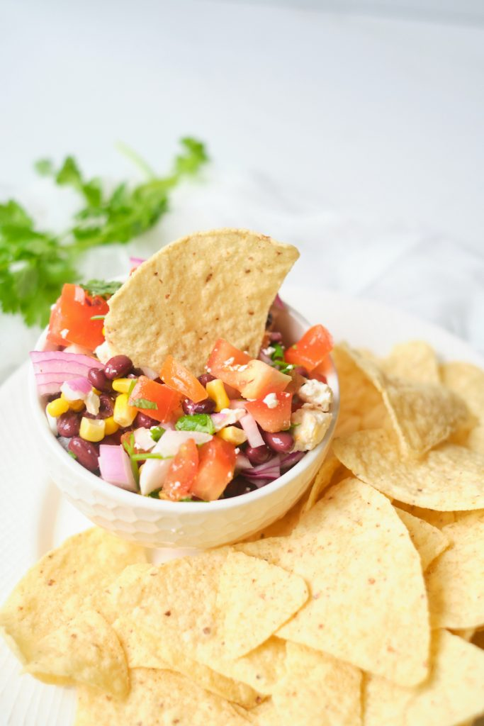 A tortilla chip garnishes a bowl of feta black bean and corn dip with a plate of tortilla chips surrounding it