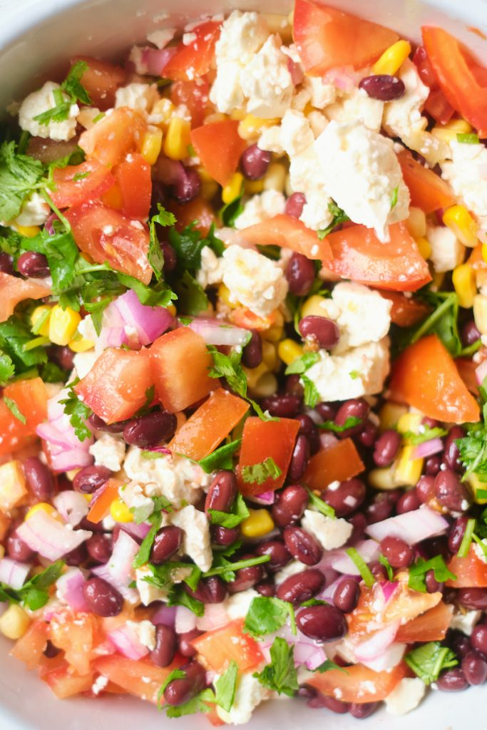 close up of ingredients in a black bean corn feta dip includes tomatoes, feta cheese, cilantro, red onions, black beans and corn