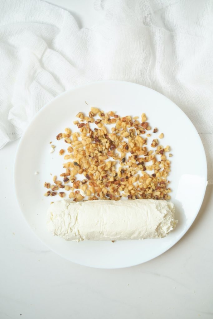 A fresh goat cheese log on a plate with chopped walnuts before rolling to cover the cheese log