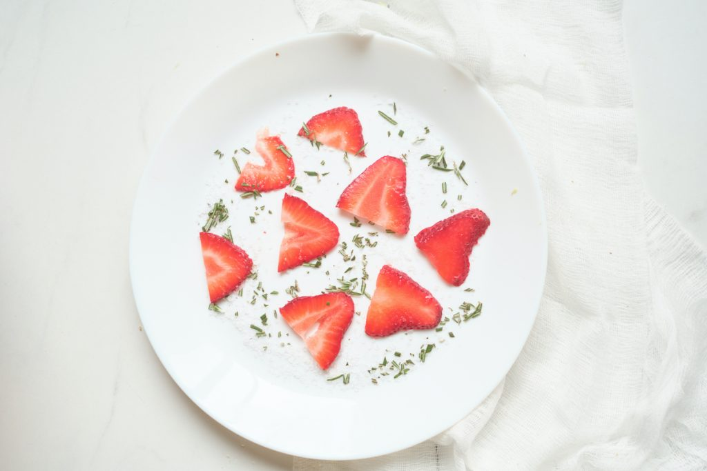 Fresh strawberry slices and dried rosemary spread evenly on a white dinner plate before rolling a cheese log in