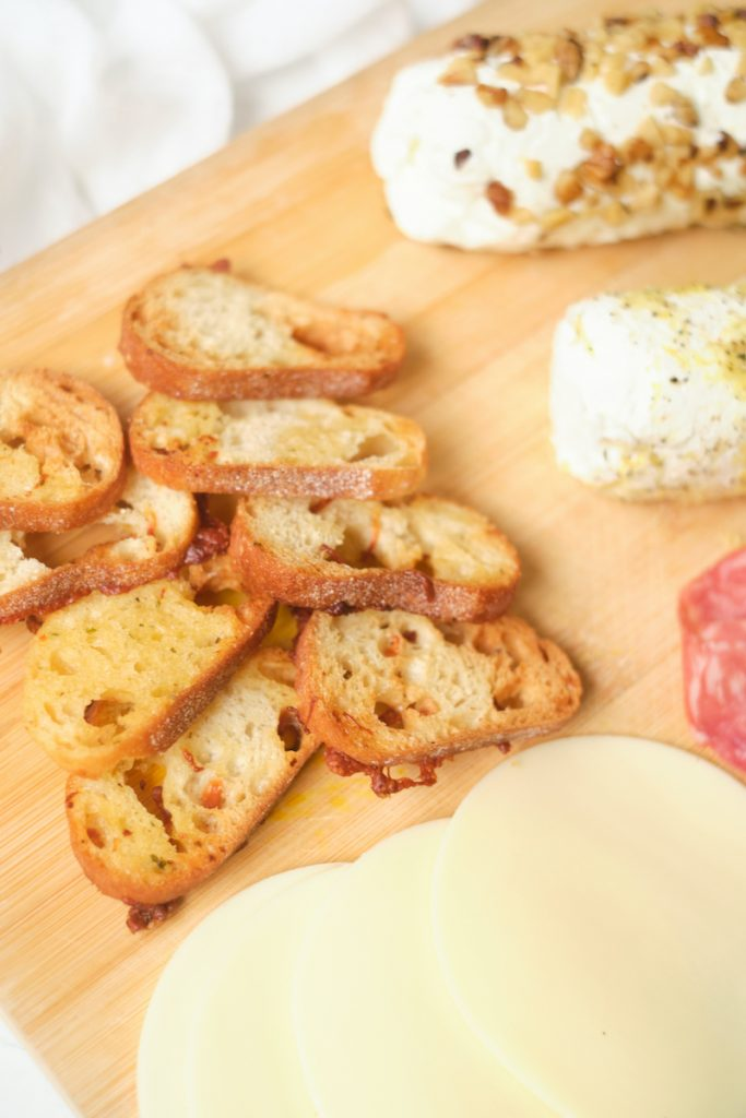 A selection of homemade baguette crisps on a cheese board with cheese and meat in view
