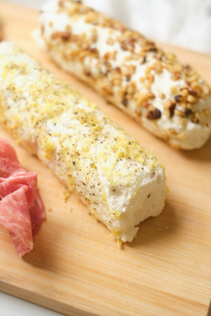 Close up of a cheese board with meat and two goats cheese logs covered in lemon zest and pepper and in chopped walnuts and honey