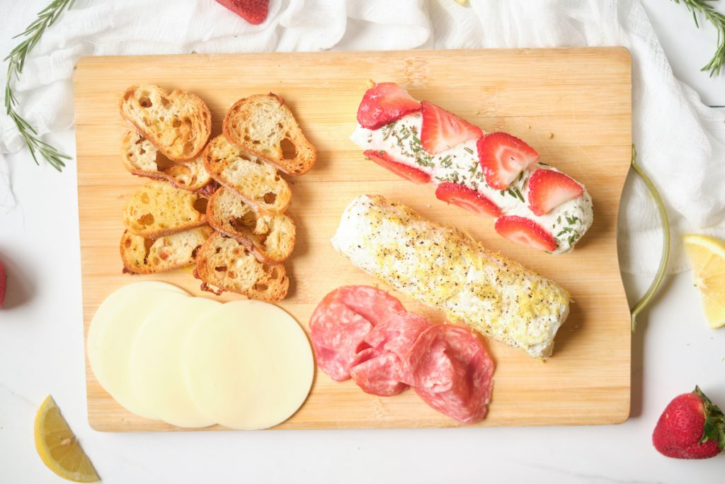 A birds eye view of a cheese board with homemade baguette crisps, cheese slices, meat, and flavored goat cheese logs