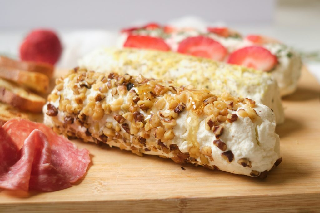 A cheese board with three flavors of goat cheese logs include walnut-honey, lemon-pepper, and strawberry-rosemary