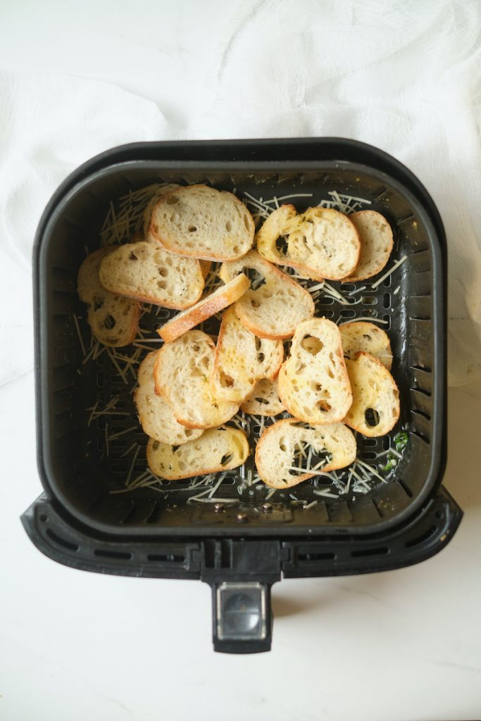 baguette slices and rosemary in an air fryer basket before baking