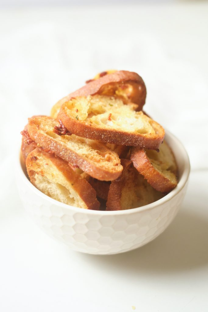 a bowl containing homemade garlic Parmesan crostini from a baguette