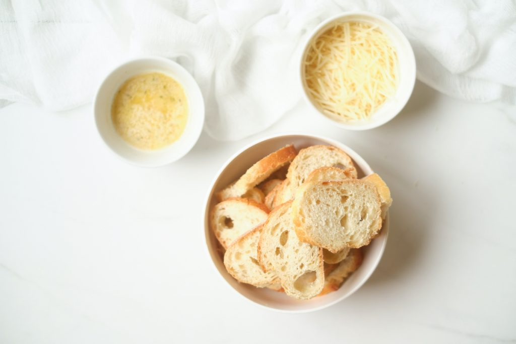 A bowl of sliced baguette, a bowl of Parmesan cheese shreds, and a bowl of melted garlic butter on a white counter to show ingredients for homemade crostini