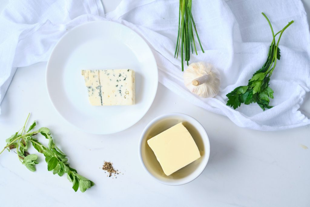 ingredients to make garlic blue cheese butter on a white table including butter, fresh herbs, garlic, gorgonzola cheese, and fresh black pepper