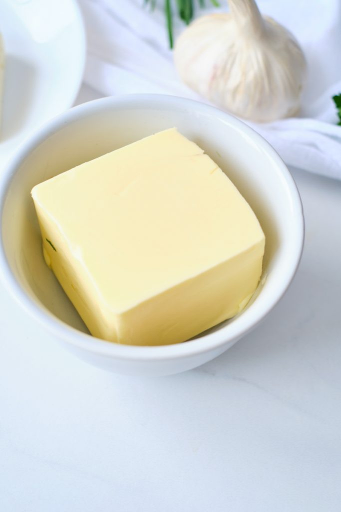 A square of butter in a white dish with a clove of garlic in the background