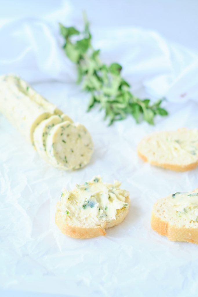 slices of compound garlic gorgonzola butter spread on baguette slices, with fresh herbs in the background