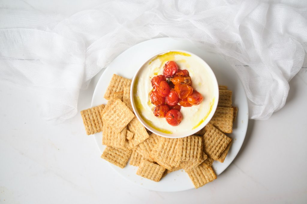 A bowl of whipped feta dip piled with roasted cherry tomatoes on a platter with crackers